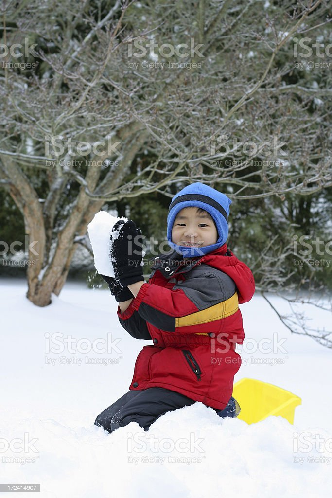 Cute young Asian boy happily playing with a snowball royalty-free stock photo