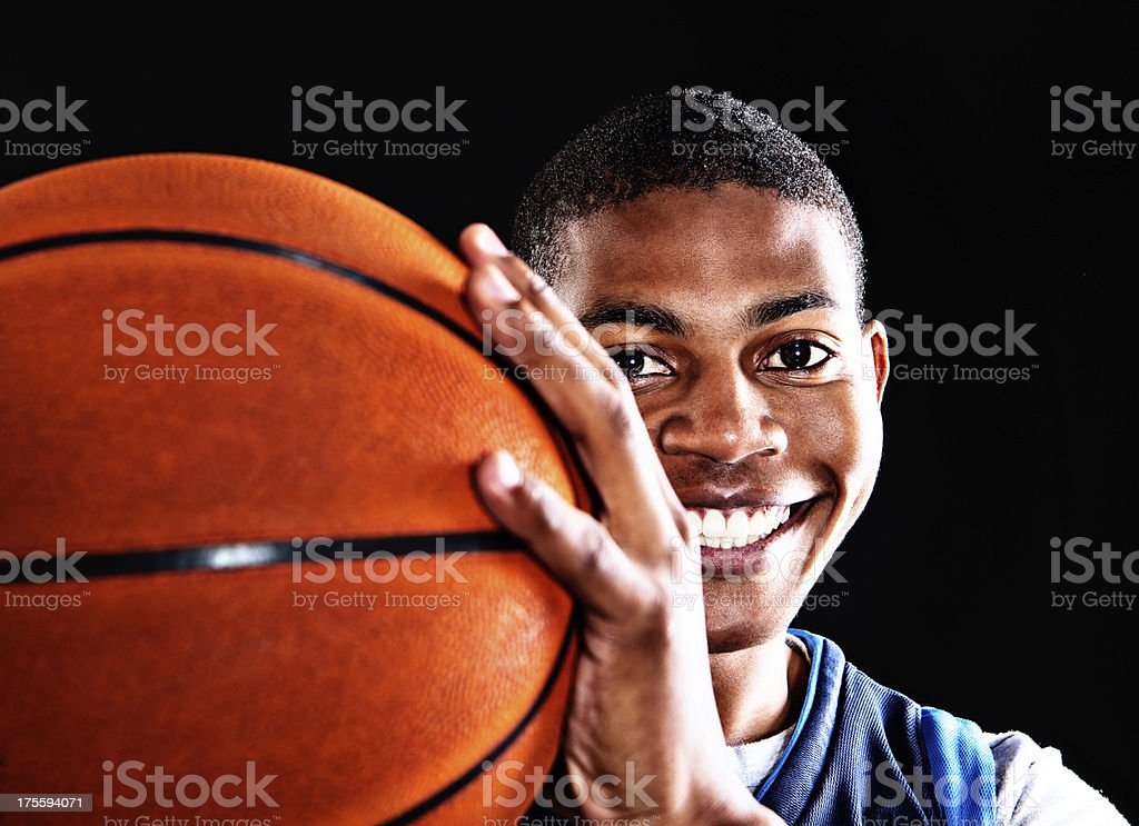 Cute young basketball player ready to pass the ball smiles stock photo