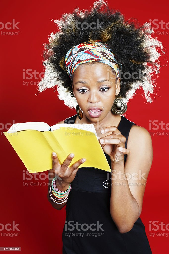 Cute young beauty is amazed by contents of yellow-covered book royalty-free stock photo