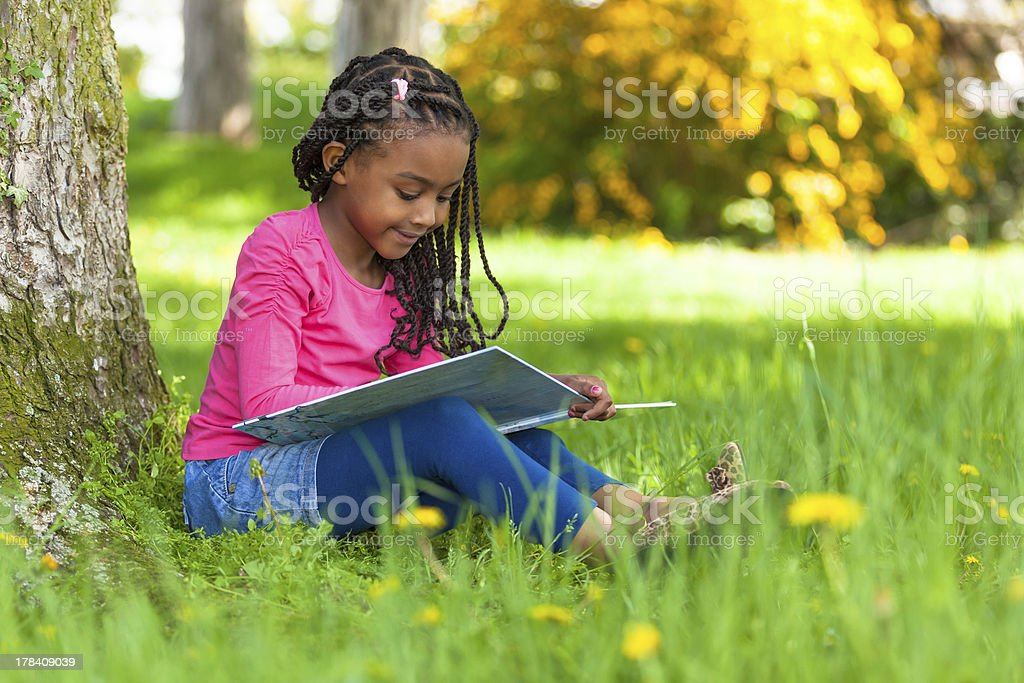 Cute young black little girl reading a book stock photo