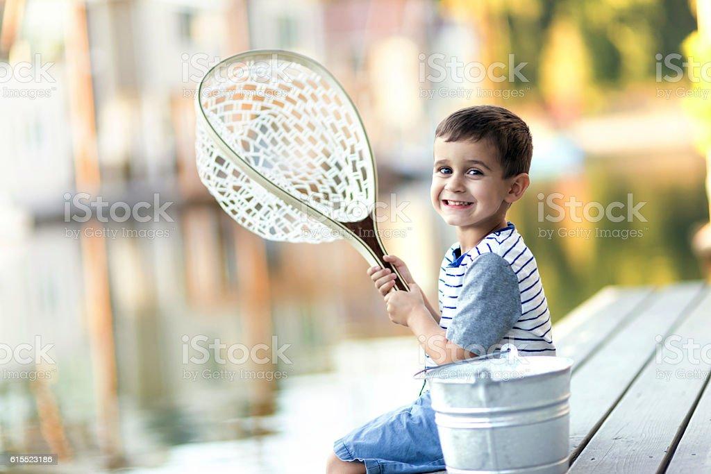 Cute young boy holding a fishing net in a marina stock photo