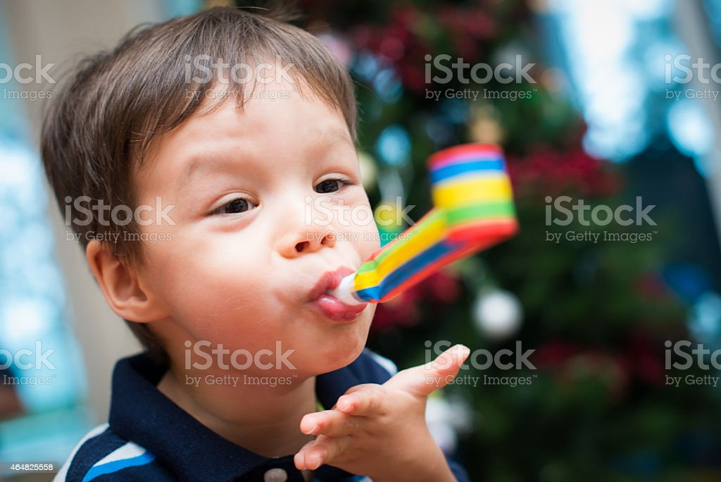 Cute young boy plays with a party blower at Christmas stock photo