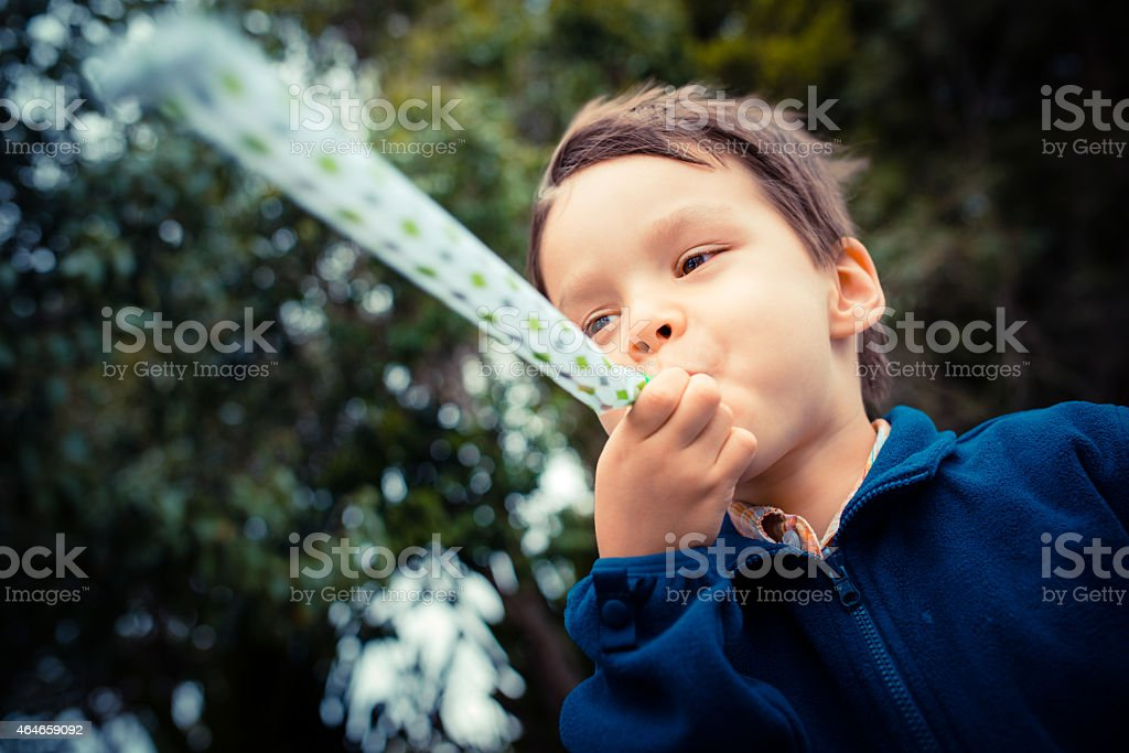 Cute young boy plays with a party blower stock photo
