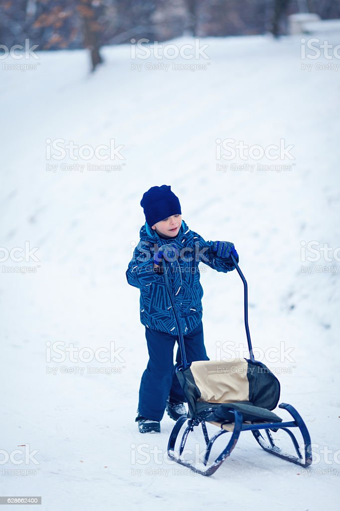 Cute young boy sprayed with snow as he is sledging stock photo
