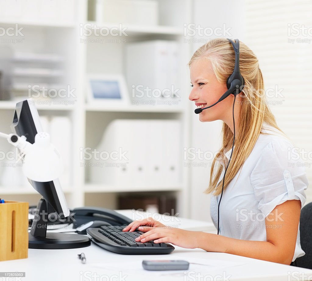 Cute young business woman working on computer, wearing headset stock photo