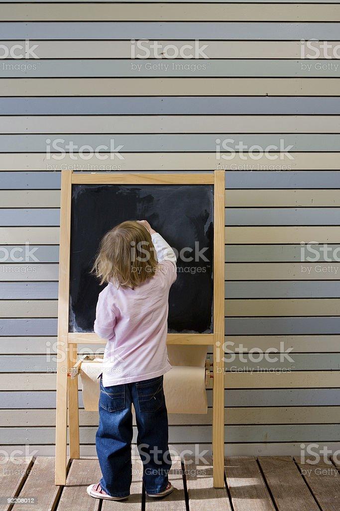 Cute young caucasian boy writing on a blackboard stock photo