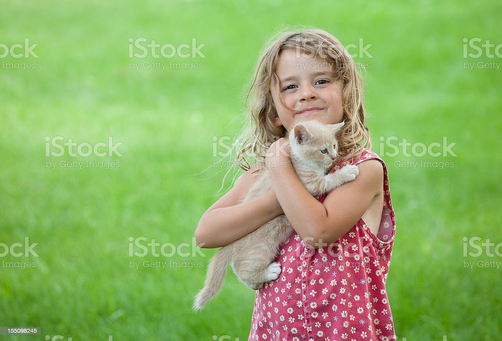 Cute Young Caucasian Girl Holding Kitten stock photo