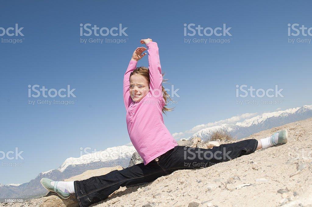 Cute Young Caucasian Girl Stretching Outside on a Hilltop stock photo