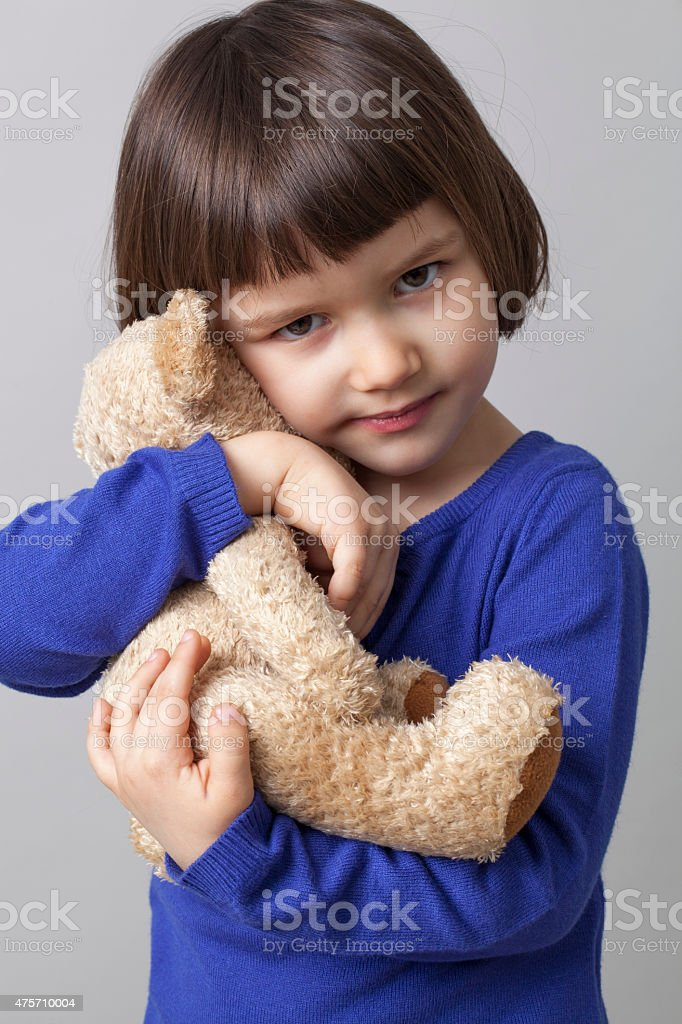 cute young child higging her comforter for relaxation and softness stock photo
