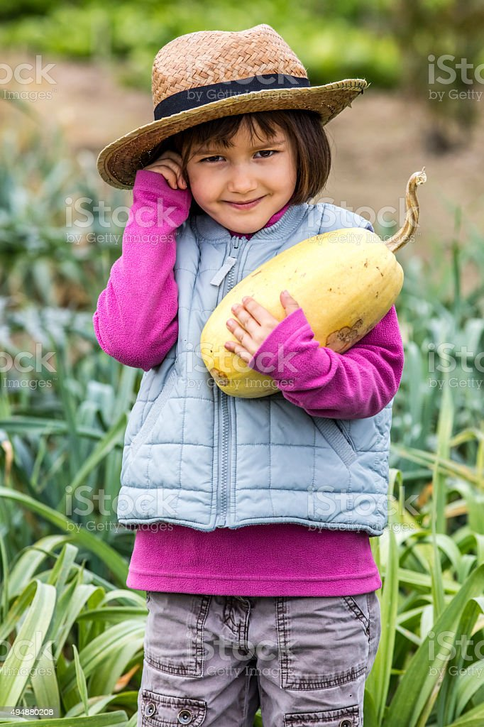 cute young child smiling after picking organic squash from garden stock photo