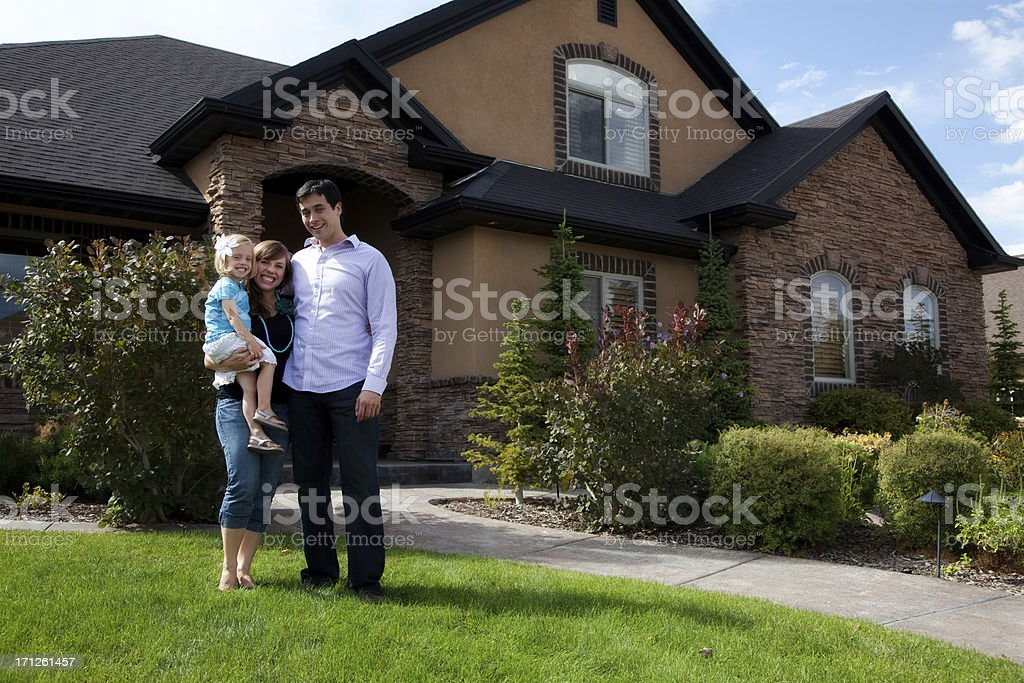 Cute Young Couple and Child with Beautiful Home royalty-free stock photo