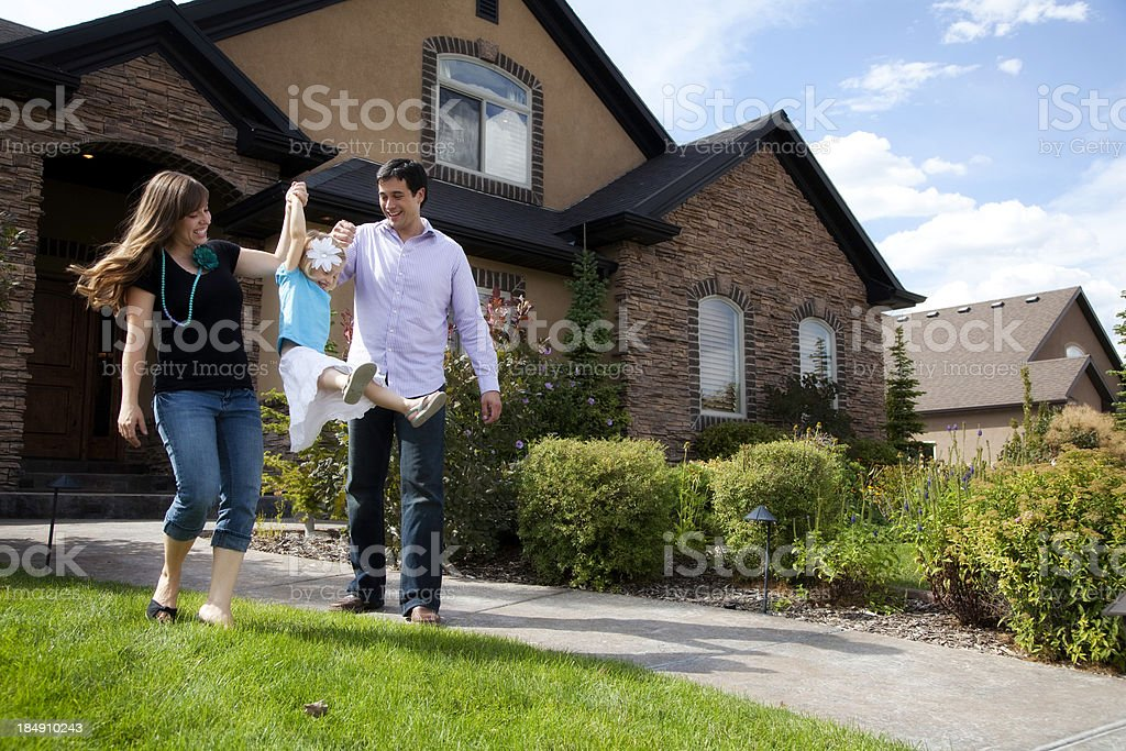 Cute Young Couple and Child with Beautiful Home stock photo