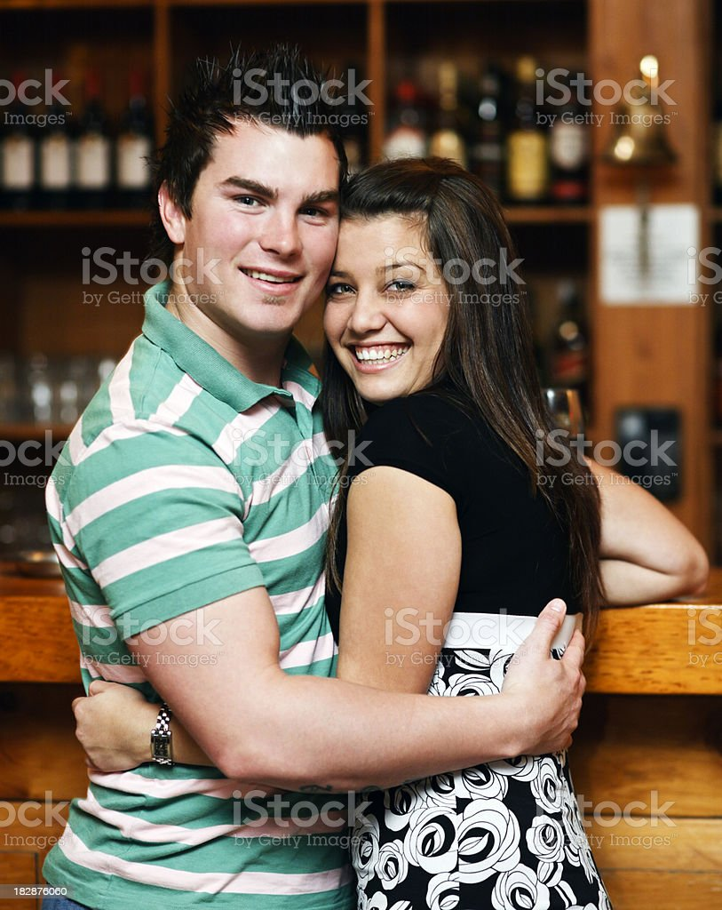 Cute young couple embrace in trendy wood panelled bar royalty-free stock photo