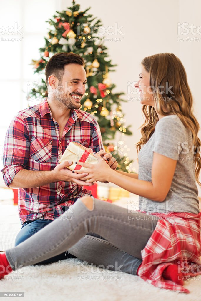 Cute, young couple exchanging Christmas presents on Christmas morning stock photo