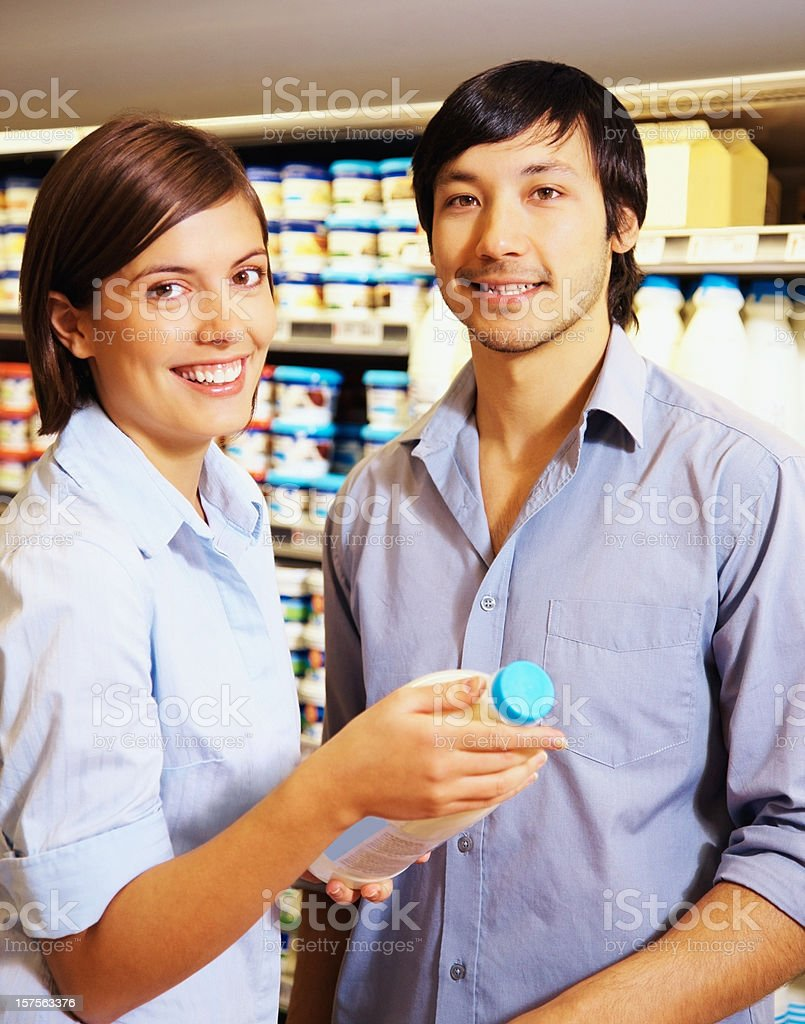 Cute young couple holding milk bottle at a supermarket royalty-free stock photo