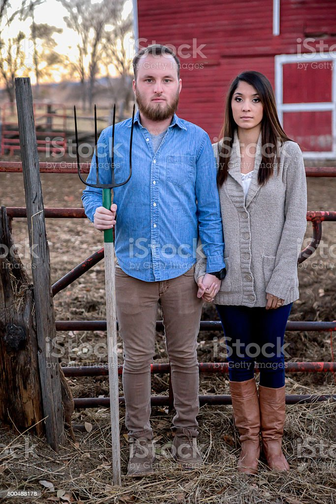 Cute Young Couple Posing at Farm with Pitchfork stock photo