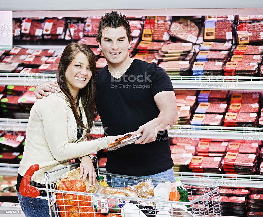 Cute young couple shop for meat in supermarket royalty-free stock photo