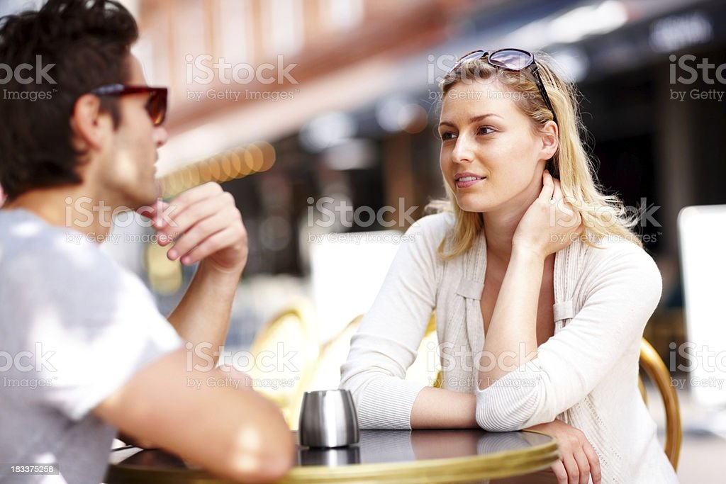 Cute young couple sitting at an open cafe royalty-free stock photo