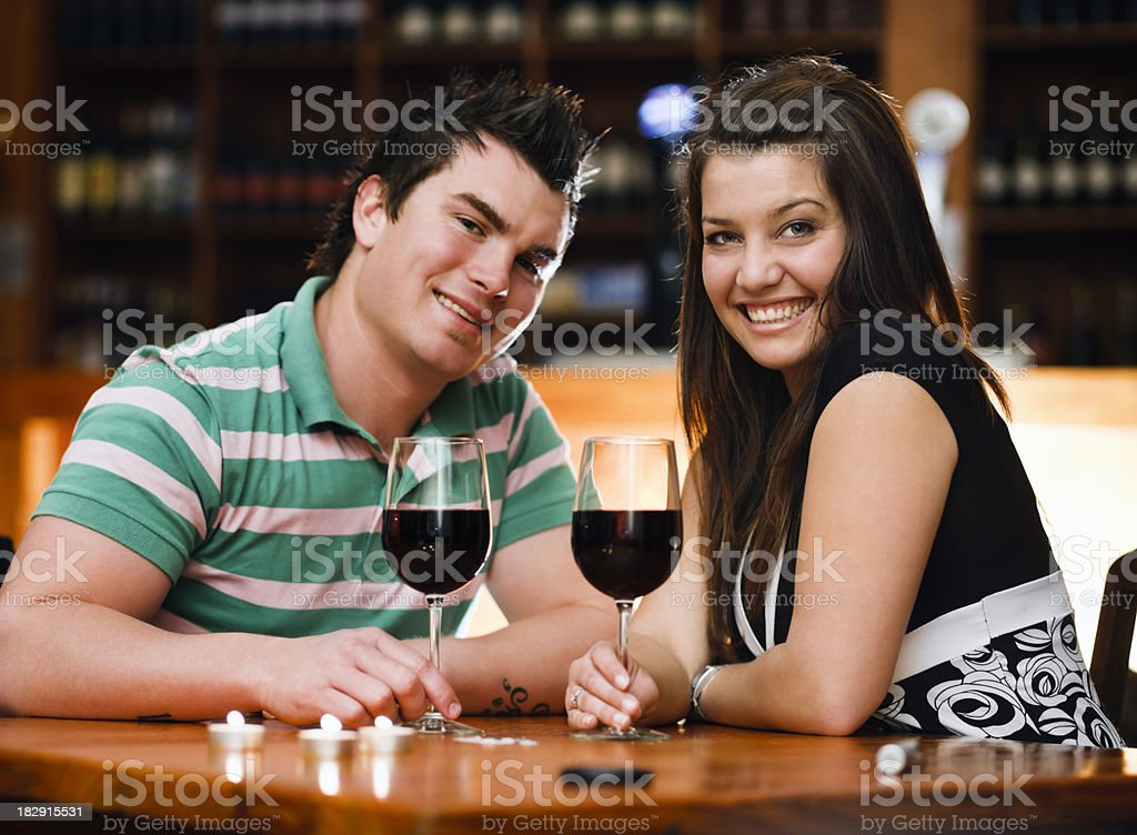 Cute young couple socialize at table with red wine royalty-free stock photo