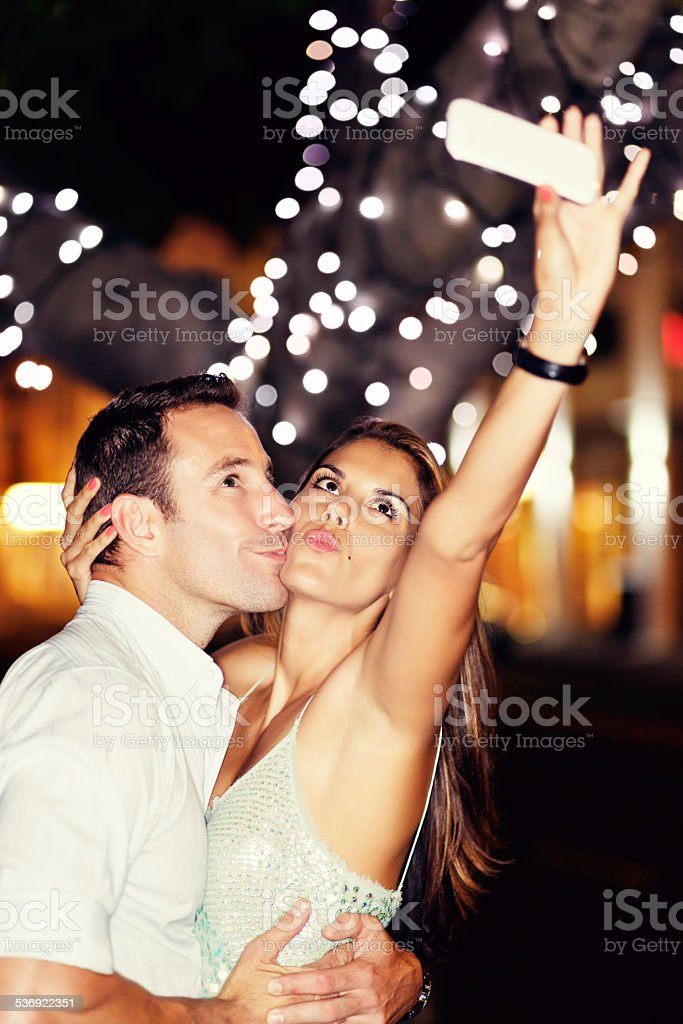 Cute young couple take trout-pout selfie under twinkling lights stock photo