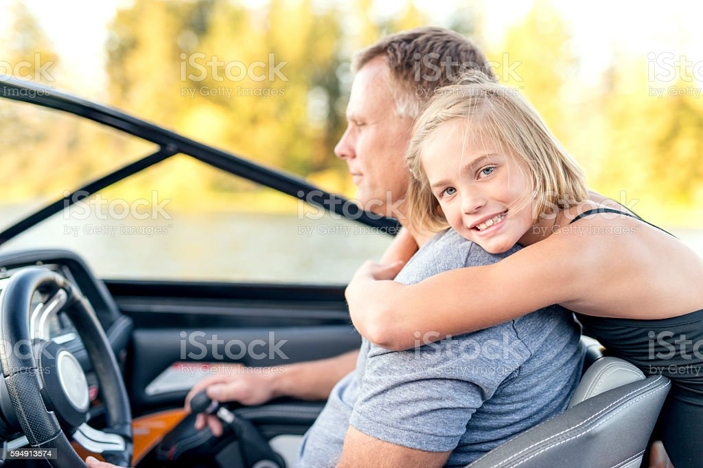 Cute young daughter hugging her father stock photo
