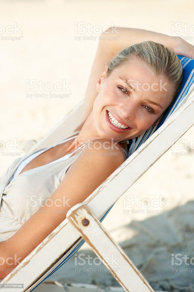 Cute young female relaxing on a deck chair stock photo