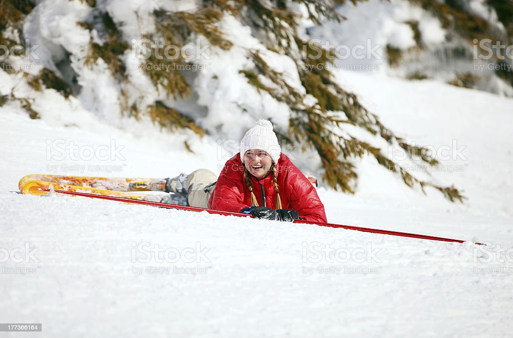 Cute young female skier looking at camera after falling down stock photo