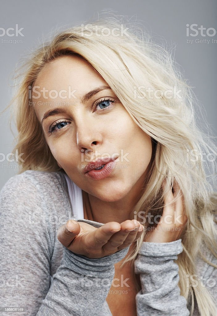 Cute, young girl blowing you a kiss stock photo