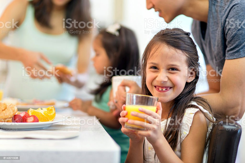 Cute young girl drinking orange juice and smiling stock photo