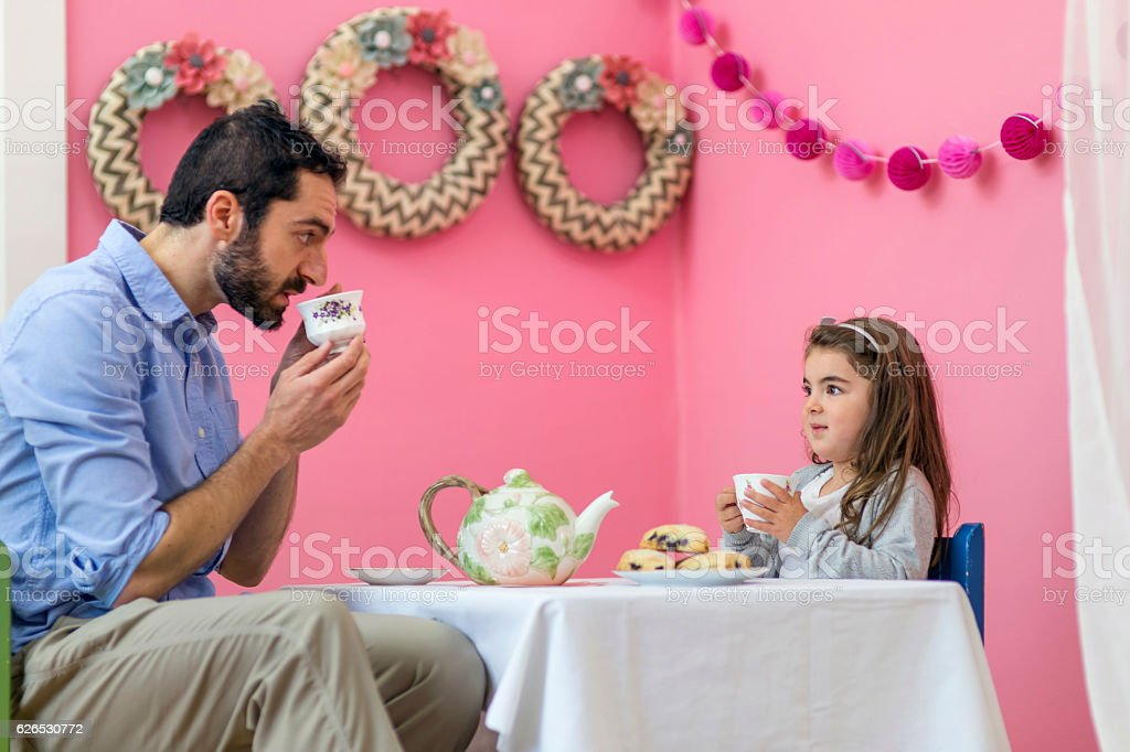 Cute young girl having a tea party with her dad stock photo