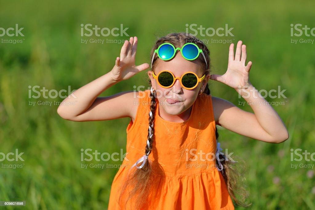 Cute young girl in sun glasses hamming having fun outdoors. stock photo
