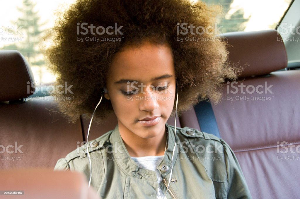 Cute young girl listening to Music stock photo