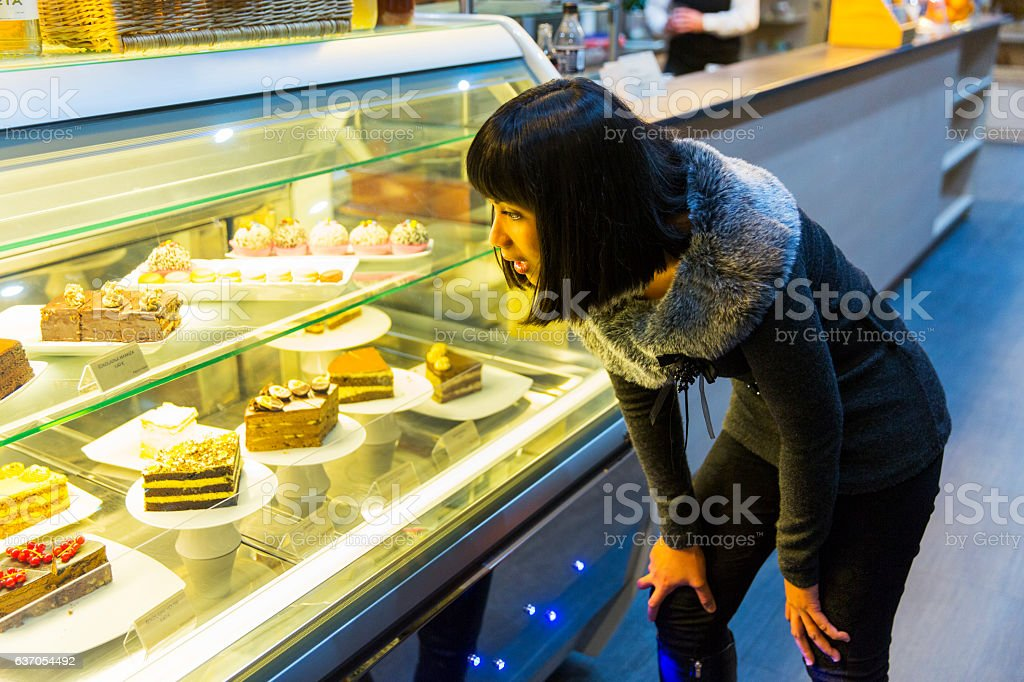 Cute young girl looking at display window with cakes stock photo