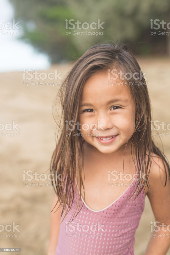 Cute young girl posing for camera on Hawaii beach stock photo