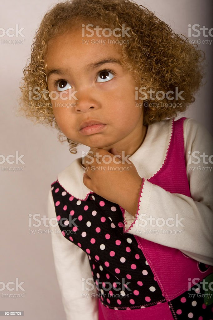 Cute young girl thinking stock photo
