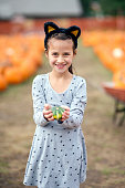Cute young girl wearing cat ears and holding a pumpkin