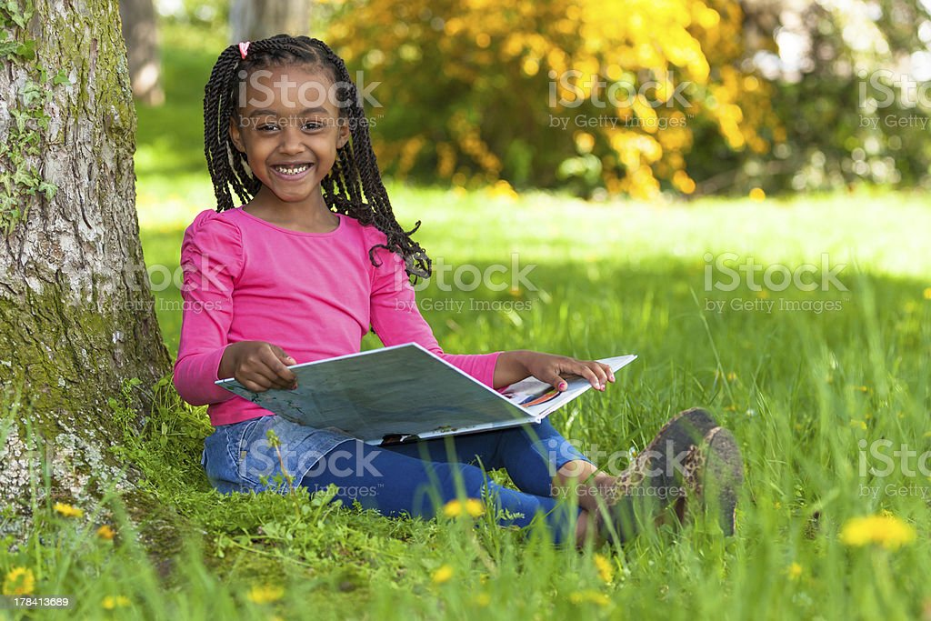 Cute young little girl reading book in park stock photo