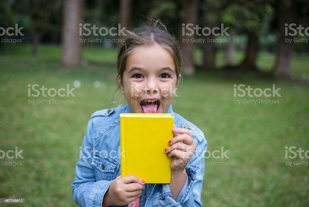 Cute young little girl with a new book. stock photo