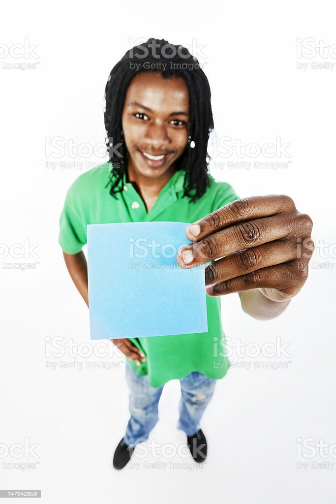 Cute young man smilingly holds up blank blue adhesive note stock photo