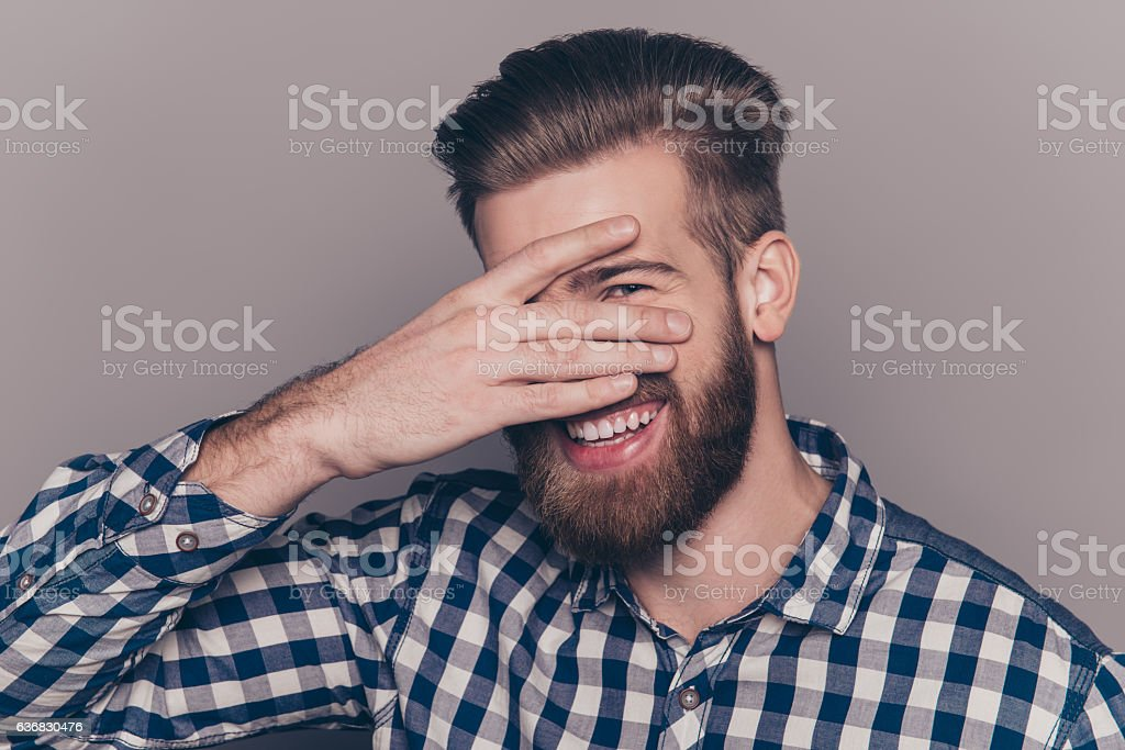 cute  young man with beard hiding his face with palms stock photo