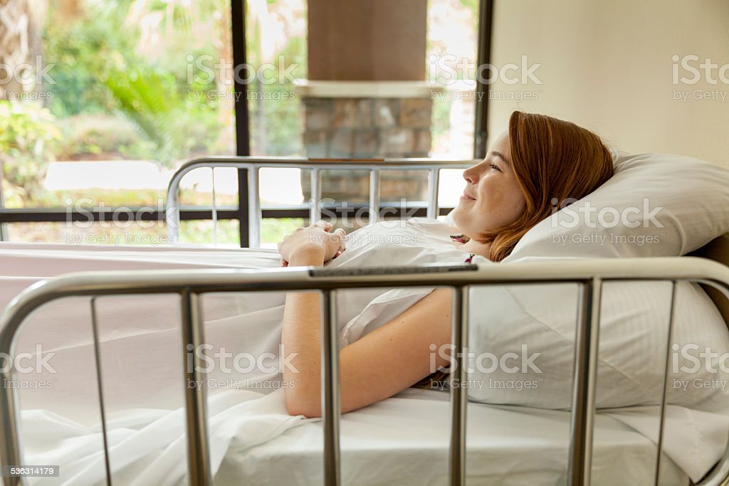 Cute Young Teenager Smilling in a Hospital Bed stock photo