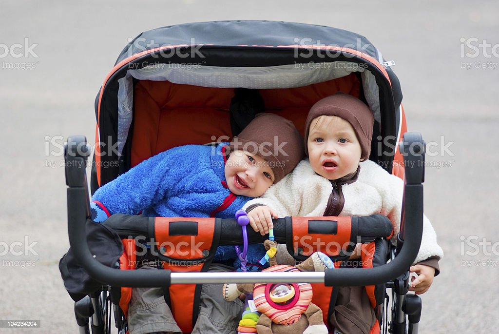 Cute young twins in hats in a double stroller on a street stock photo