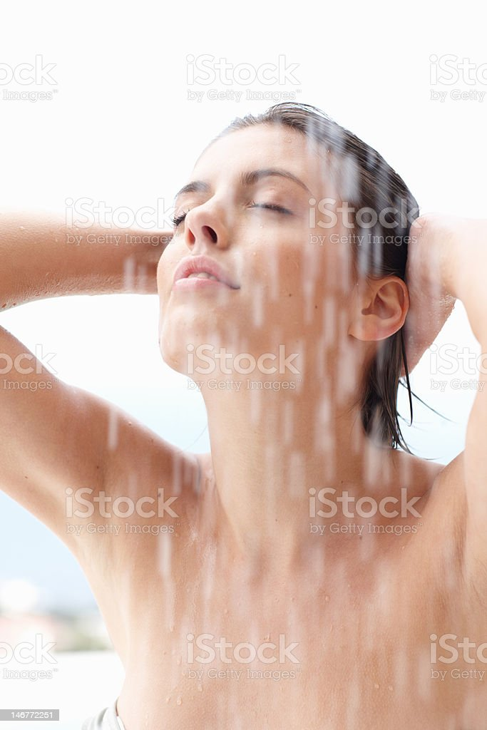 Cute young woman bathing under an outdoor shower stock photo