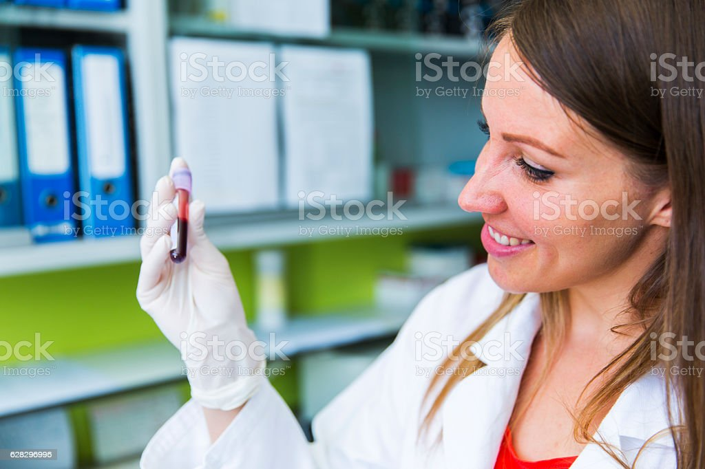 Cute young woman doctor holding vial with blood sample stock photo
