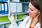 Cute young woman doctor holding vial with blood sample