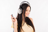 Cute young woman enjoying music on headphones, smiling