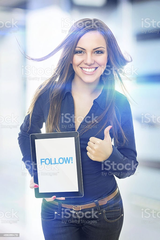 Cute young woman holding tablet that states follow royalty-free stock photo