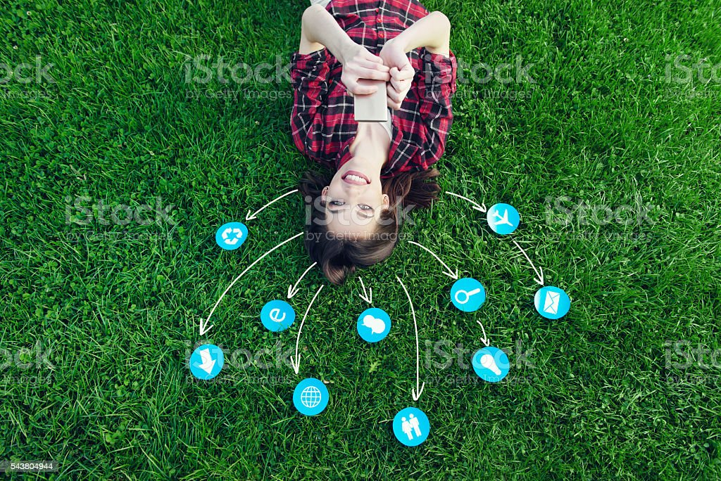 Cute young woman laying on the grass, using cell phone stock photo