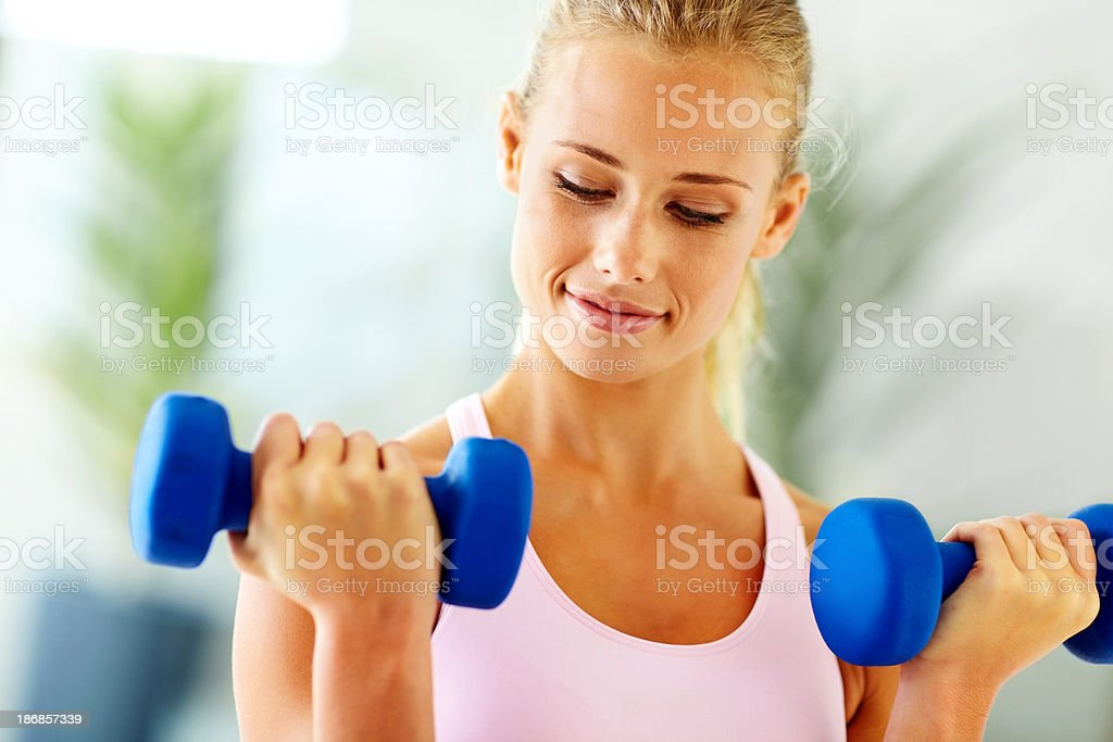 Cute young woman lifting weights royalty-free stock photo