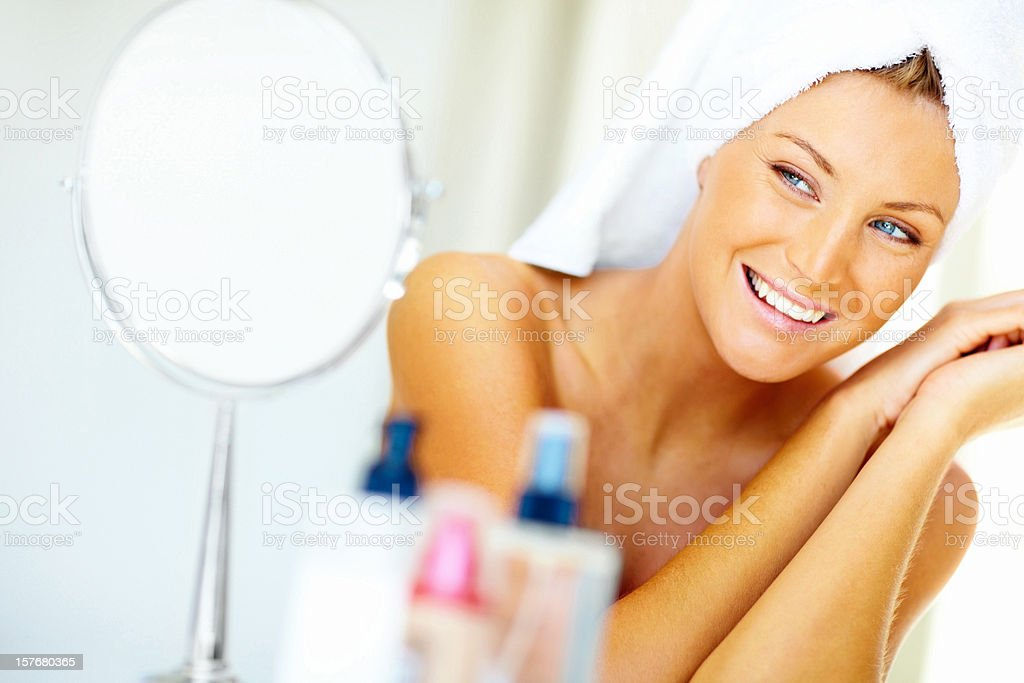 Cute young woman looking her face in a mirror royalty-free stock photo
